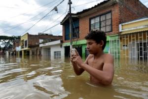 [포토] 홍수 속에서 휴대전화를 확인하는 콜롬비아의 한 남성