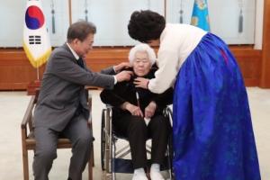 [서울포토] 위안부 피해 할머니 옷 만져주는 문 대통령 내외