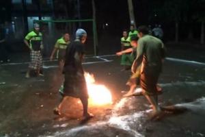 활활 타오르는 코코넛으로 맨발 축구하는 소년들