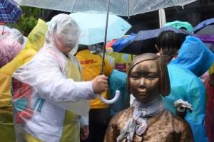 [서울포토] 소녀상 우산 씌워주는 학생