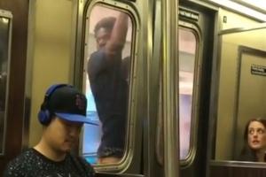 지하철 문에 매달린 채 목적지 가는 남성