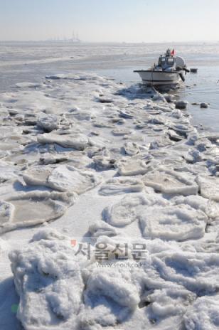 바다도 얼었다  한파가 연일 계속되는 가운데 13일 인천 영종도 앞 바다가 얼음조각들로 뒤엉켜 꽁꽁 얼어붙으면서 정박한 고깃배가 고립돼 있다. 도준석기자 pado@seoul.co.kr