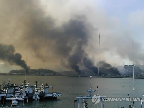 북한이 23일 오후 2시34분께 연평도 부근에 다량의 해안포를 발사해 이중 수발은 주민들이 살고있는 연평도에 떨어져 섬 일대가 검은 연기에 휩싸여 있다.  연평도=연합뉴스