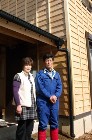 이시노마키시 시라하마에 지은 부흥 주택에서 살고 있는 가쓰야 부부가 집 앞에서 포즈를 취하고 있다.