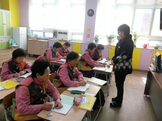 경남 하동군 고전면 고전초등학교에 입학한 7명의 할머니들이 5일 박윤희(오른쪽) 담임 교사의 수업을 받고 있다.