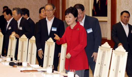 """박근혜 대통령이 29일 중견기업 대표들을 청와대로 초청해 오찬 간담회를 갖기에 앞서 참석자들을 자리로 직접 안내하고 있다. 박 대통령은 스스로 """"투자활성화복""""이라고 지칭한 빨간색 재킷을 입고 나와 눈길을 끌었다. 청와대사진기자단"""
