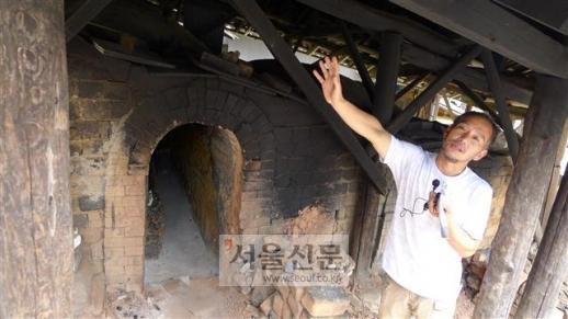 온타야키 마을의 도예가 사카모토 코지가 마을 공동가마에서 장작불로 굽는 도자기들에 대해 설명하고 있다.