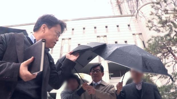 다큐멘터리 영화 '자백' 스틸컷 최승호PD(왼쪽)와 우산 속 원세훈 전 국정원장.