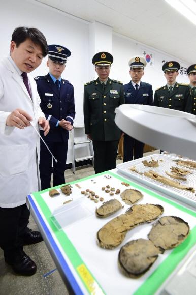 6·25 전쟁 중 전사한 중국군 유해 입관식이 20일 인천에 마련된 '중국군 유해 임시안치소'에서 거행된 가운데 국방부 유해발굴감식단 관계자가 주한 중국대사관 국방무관 두눙이(왼쪽 세 번째) 소장 등 중국 측 관계자들에게 유해에 대해 설명하고 있다. 사진공동취재단