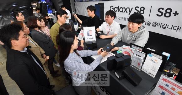 삼성전자의 최신 스마트폰 '갤럭시S8'의 일반 판매가 시작된 21일 서울 종로구 세종대로 KT올레스퀘어에서 고객들이 휴대전화를 개통하고 있다. 손형준 기자 boltagoo@seoul.co.kr