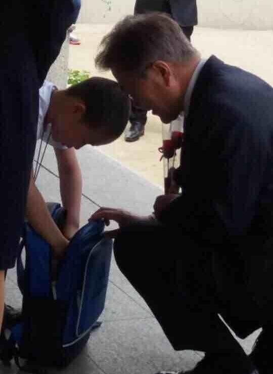 사인 종이 찾는 어린이를 쪼그리고 앉아기다리는 문재인 대통령