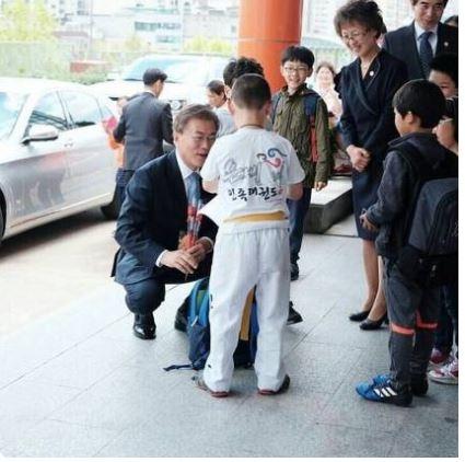 사인 종이 찾는 초등학생을 쪼그려 앉아 기다리는 문재인 대통령
