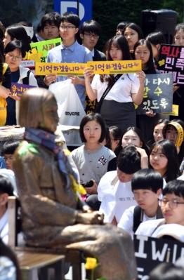 """위안부 소녀상 앞에서 """"기억하겠습니다"""" 다짐하는 학생들 17일 서울 일본대사관 앞에서 열린 정기수요집회에 참석한 학생들이 일본을 규탄하는 피켓을 들고 있다. 2017.5.17 박지환기자 popocar@seoul.co.kr"""