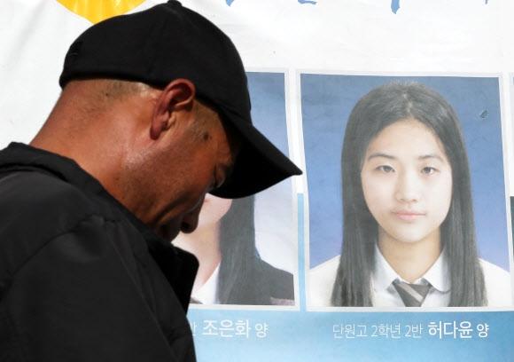 세월호 참사 미수습자인 단원고 허다윤양의 아버지 흥환씨가 19일 전남 목포신항 '미수습자 가족 만남의 장소'에 걸려 있는 딸의 사진 앞에서 고개를 숙이고 있다. 목포 연합뉴스