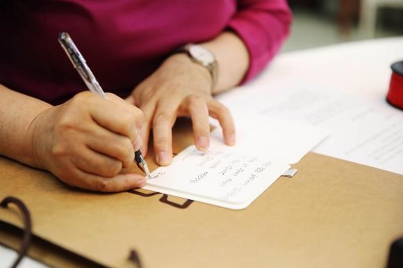 김정숙 여사가 여야 5당 원내대표들에게 줄 손편지를 쓰고 있다. 청와대 제공