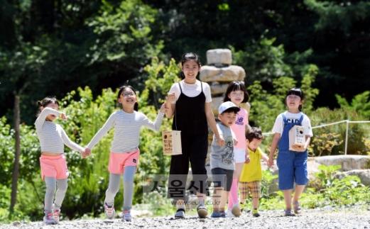 강원 철원군 동송읍에서 온 어린이들이 산새 학교에서 직접 만들고 각자 이름을 쓴 둥지를 들고 지장산 골짜기 적당한 장소에 설치하기 위해 숲길로 들어가고 있다.