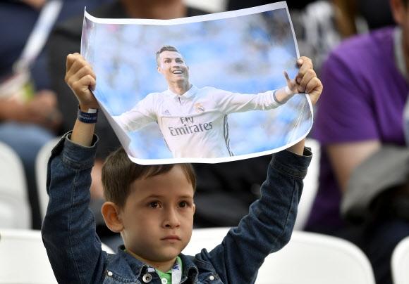 어린이 팬이 18일(현지시간) 러시아 카잔 아레나에서 열린 2017 국제축구연맹(FIFA) 컨페더레이션스컵 A조 멕시코와의 첫 경기 도중 포르투갈의 주포 크리스티아누 호날두의 포스터를 든 채 응워낳고 있다. 카잔 AP 연합뉴스