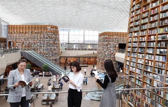 지난 달 31일 서울 강남구 코엑스몰에 문을 연 '별마당 도서관'을 찾은 사람들이 책을 읽고 있다. 이 도서관은 2층 규모로 5만권에 달하는 서적을 보유하고 있다. 연합뉴스