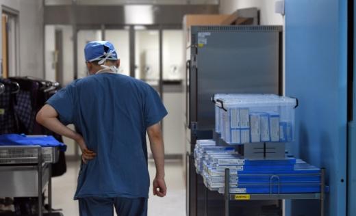 경기남부권역외상센터 이국종 소장이 장시간의 수술을 마치고 허리를 두드리며 환자 가족들에게 결과를 알려 주기 위해 걸어가고 있다.