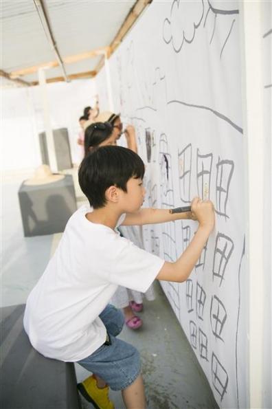 작가가 동네를 돌면서 그린 이미지 위에 벽화놀이를 하는 어린이들.