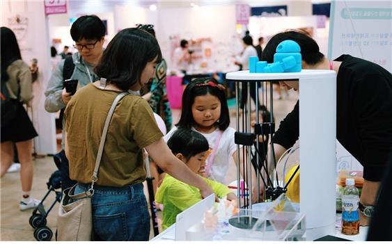 지난 5월 '서울 디자인 페스타'에 참가한 '팹랩서울'의 3D 프린팅 제품을 방문객들이 체험해 보고 있다. 팹랩서울 제공