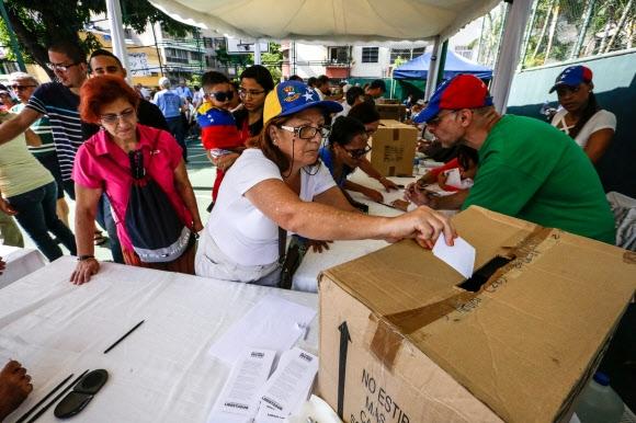 베네수엘라 야권 비공식 개헌찬반 투표… 친정부 단체 총격에 1명 사망  베네수엘라 국민들이 16일(현지시간) 수도 카라카스에서 개헌 찬반 투표에 참여하고 있다. 이번 투표는 우파 야권 연합 국민연합회의(MUD)가 니콜라스 마두로 대통령의 개헌에 대한 여론을 묻고자 독자적으로 기획한 것으로, 법적 정당성은 없다. 야권은 710만명이 참가해 대부분 반대표를 던졌다고 주장했다. 이날 카라카스 서부 카티아 투표소에서는 친정부 단체의 총격으로 1명이 사망하고 4명이 부상당했다. 마두로 정부는 오는 30일 선거를 통해 의원 545명을 뽑은 뒤 국민투표를 통해 개헌안을 확정할 방침이다. 카라카스 EPA 연합뉴스
