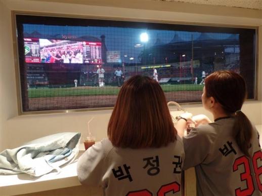 지난 12일 인천SK 행복드림구장 '끼리끼니존' 을 찾은 직장인 김나영(28·왼쪽)씨와 권민경(25)씨가 포수의 눈높이에 마련된 관중석에서 그라운드를 바라보며 경기에 집중하고 있다. 한재희 기자 jh@seoul.co.kr