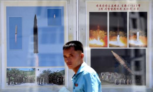 """11일 평양역 인근의 미사일 선전물 앞을 지나가는 북한 주민이 카메라를 응시하고 있다. 선전물에는 미사일 발사 장면과 함께 """"대륙간 탄도 로케트 화성-14형 2차 시험 발사에서 또다시 성공""""이라는 문구가 적혀 있다.  연합뉴스"""