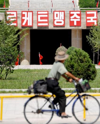 11일 평양 시내의 '로케트 맹주국'이라고 쓰인 선전물 앞에 북한 주민이 자전거를 타고 지나가고 있다. 교도통신은 지난달 북한의 대륙간탄도미사일(ICBM) 발사 후 이런 선전물이 설치된 것으로 보인다고 설명했다.  연합뉴스