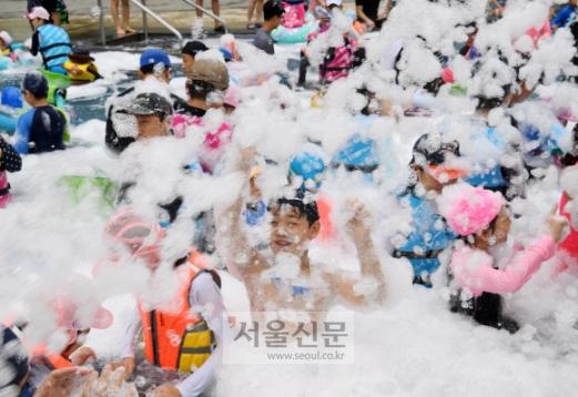 웅진플레이도시가 13일 오전 경기도 부천시 원미구 웅진플레이도시 써니파크에서 '8월의 크리스마스'이벤트를 진행했다.수영장에 버블 눈을 뿌려 한여름에 눈 내리는 장면을 연출하자 물놀이장을 찾은 어린이들리 신기해하며 즐거워하고 있다. 이호정 전문기자hojeong@seoul.co,.kr