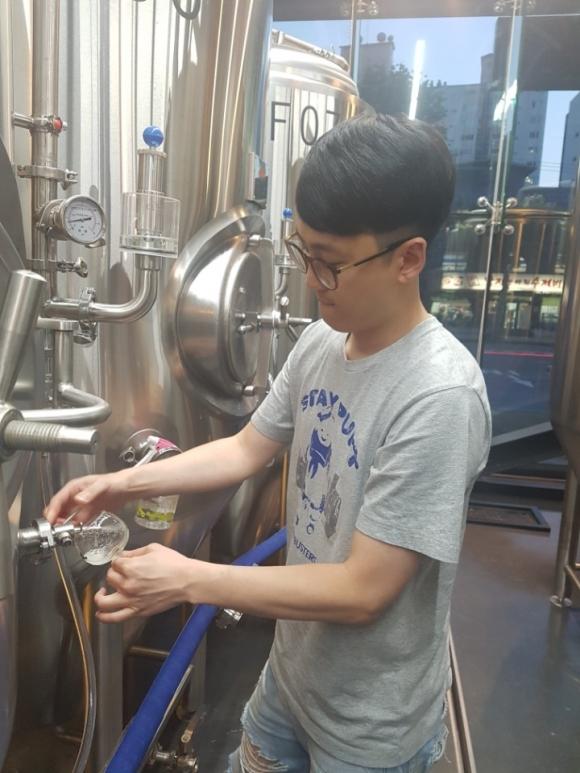 이인호 대표가 서울 마포구 미스터리양조장에서 발효조에 보관 중인 맥주를 따르고 있다.
