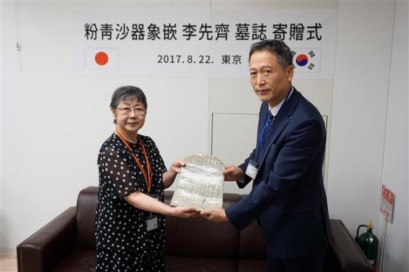 지난달 22일 일본 도쿄에서 열린 기증식에서 소장자 도도로키 구니에(왼쪽)씨가 김흥동 국외소재문화재재단 사무총장에게 묘지를 전달하고 있다. 국외소재문화재재단 제공