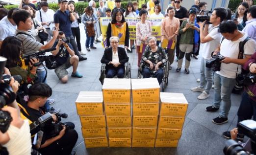 1300번째 수요일… 위안부 할머니, 日대사관에 207만명 서명 전달  일본군 위안부 문제 해결을 요구하며 1992년 시작해 26년째 이어지고 있는 '일본군 성노예제 문제 해결을 위한 정기 수요시위'가 13일로 1300회를 맞았다. 이날 서울 종로구 수송동 주한 일본대사관 앞에서 열린 1300차 수요시위에서 휠체어를 탄 김복동(왼쪽·91) 할머니와 길원옥(89) 할머니가 일본군 성노예제 문제 해결을 촉구하는 내용의 '세계 1억인 서명운동' 2차분 155개국 206만 9760명의 서명지를 일본대사관 측에 전달하고 있다.  박지환 기자 popocar@seoul.co.kr