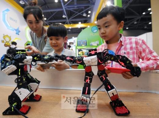 국제로봇산업대전 16일까지  13일 경기 고양시 일산 킨텍스에서 열린 '2017 로보월드 국제로봇산업대전'에서 어린이들이 로봇을 직접 조종하고 있다. 전시회에서는 16개국 150여개사가 오는 16일까지 제조용과 서비스용 로봇 등을 선보인다. 박윤슬 기자 seul@seoul.co.kr