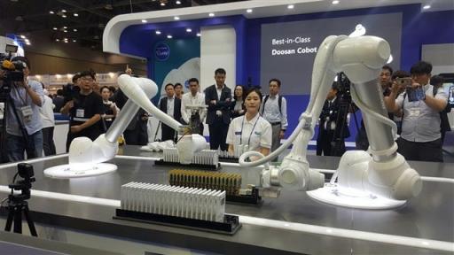 지난 13일 경기 고양 킨텍스에서 열린 '2017 로보월드'의 두산로보틱스 전시장에서 산업용 협동로봇들이 칩을 주고받으며 정리하는 작업을 시연하고 있다.