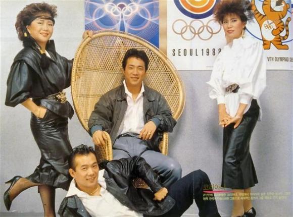 유럽에서 활동하던 4인조 그룹 '코리아나'는 서울올림픽 공식 가요 '손에 손잡고'를 가지고 21년 만에 고국에 금의환향했다. 잡지 화보 촬영을 위해 서울올림픽 포스터 앞에서 포즈를 취했다.