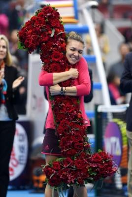 루마니아 Simona Halep가 7일(현지시간) 중국 베이징에서 열린 '중국 오픈 테니스 토너먼트' 여자 준결승전에서 라트비아의 Jelena Ostapenko를 상대로 이기고 1위로 랭킹된 후 장미로 장식된 숫자 '1' 부케를 안고 기뻐하고 있다. AFP 연합뉴스