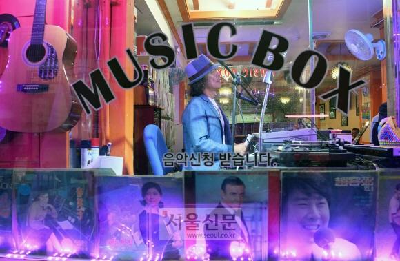 DJ 장민욱씨가 거리에서 보이는 음악감상실 뮤직박스에서 손님들의 음악신청 사연을 소개하고 있다.