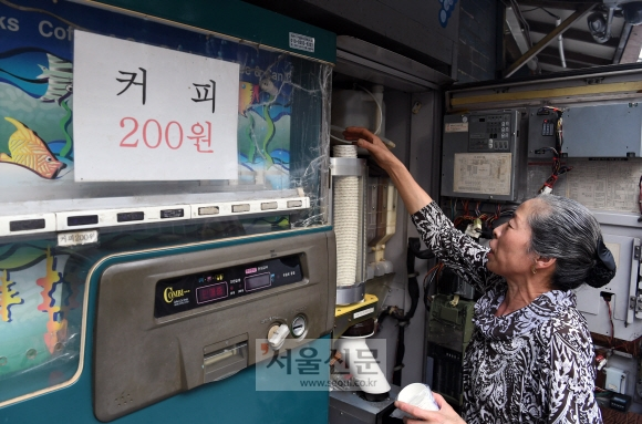 돌아가신 시어머니 커피자판기를 물려받아 2대째 운영하고 있는 고한순(63)씨가 자판기를 청소하고 재료를 보충하고 있다.