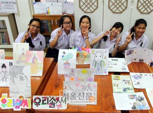 태국 싸라윗타라 학교 한국어반 5학년 학생들이 한국문화 수업 시간에 만든 그림들을 보여주면서 활짝 웃고 있다. 그림은 다양한 한글을 활용하거나 한국 문화를 그려 완성한 것들이다.