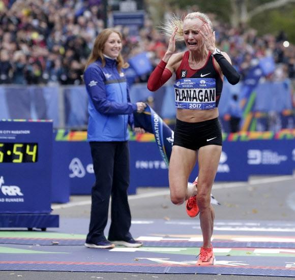 미국 선수로는 40년 만에 우승을 차지한 샬레인 플래너건(가운데)이 5일 뉴욕마라톤 여자부 결승선을 감격에 겨워 울음을 터뜨리며 통과하고 있다.  뉴욕 AFP 연합뉴스