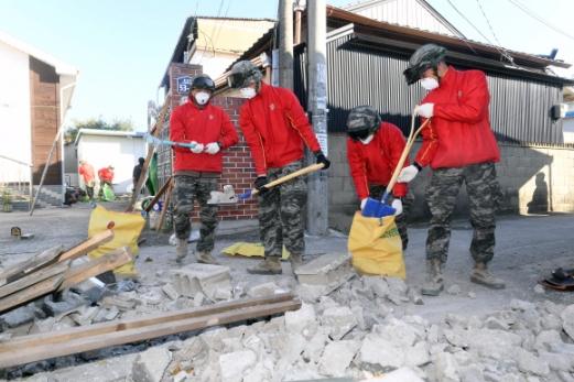 해병대원들 복구 구슬땀  경북 포항에 5.4 규모의 지진이 발생한 가운데 16일 중성2리에서 해병대원들이 길에 뒹굴고 있는 부서진 벽돌 등 지진 잔해들을 자루에 담고 있다. 포항 정연호 기자 tpgod@seoul.co.kr