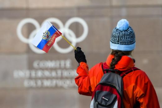 """""""러 없는 올림픽 없다""""  국제올림픽위원회(IOC)가 집행위원회를 열어 러시아 선수단의 2018 평창동계올림픽 참가를 막기로 결정한 5일(현지시간) 스위스 로잔 IOC 본부의 오륜마크 앞을 한 여성이 러시아 국기를 흔들며 지나가고 있다. 로잔 AFP 연합뉴스"""