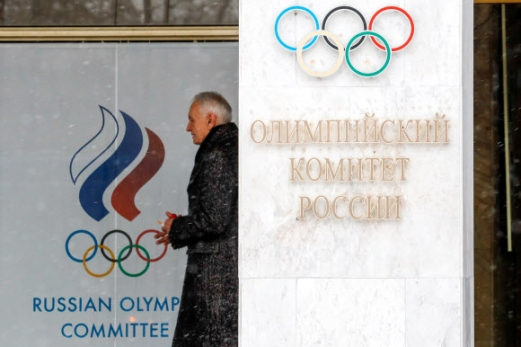 러시아에 대한 국제올림픽위원회(IOC)의 평창동계올림픽 출전 금지가 발표된 하루 뒤인 7일 모스크바 루즈네츠카야 네베레즈나야 거리에 있는 러시아올림픽위원회 외벽에 그려진 휘장 사이로 한 관계자가 지나가고 있다. 모스크바 타스통신 연합뉴스
