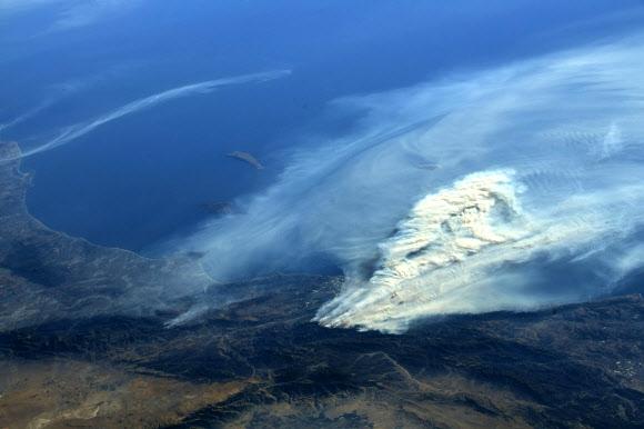 우주정거장에서 본 산불 현장  미국 항공우주국(NASA)의 우주비행사 랜디 브레스닉이 국제우주정거장(ISS)에서 찍은 미국 캘리포니아 초대형 산불 사진을 6일(현지시간) 자신의 트위터에 올렸다. 이날까지 불에 탄 면적은 약 17만 3075에이커(약 700㎢)로 서울 면적(605㎢)을 웃돈다. 랜디 브레스닉 트위터 캡처