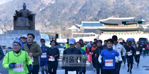 2018년 한 해의 시작을 기념해 개최한 '2018 해피뉴런(Happy New Run)' 10㎞ 마라톤 대회 참가자들이 호흡을 고르며 광화문광장 세종대왕 동상 앞을 힘차게 내달리고 있다. 박지환 기자 popocar@seoul.co.kr