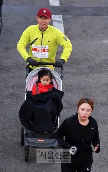 한 남성 참가자가 유모차에 딸을 태우고 마라톤 코스를 달리고 있다. 활기차고 건강한 새해를 맞이하기 위해 가족 단위로 참가한 사람들이 많았다. 정연호 기자 tpgod@seoul.co.kr