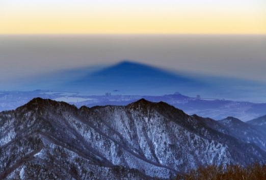 설악의 최고봉에서 굽어본 모습. 대청봉의 그림자가 화채봉 너머 속초 앞바다 쪽으로 길게 드리워져 있다. 높은 산을 저물녘에 올라야 마주할 수 있는 아주 특별한 풍경이다.