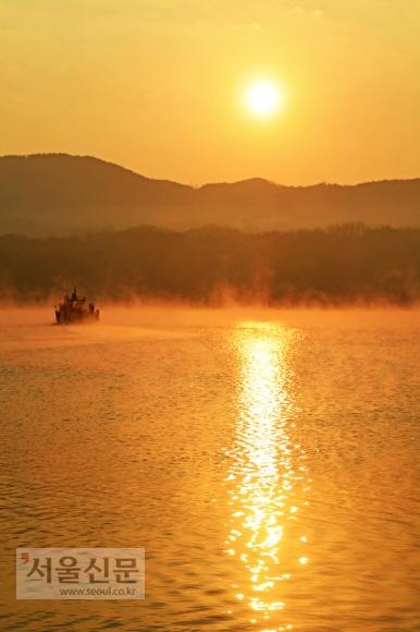 동틀 무렵, 오렌지 빛으로 물든 안동호. 박명에 일기 시작한 물안개가 솜털처럼 호수 위에 깔려 있다. 해가 늦게 뜨는 겨울철에 조금만 서두르면 만날 수 있는 풍경이다.