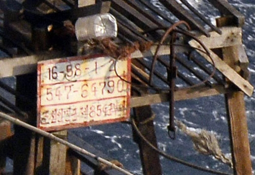지난달 일본 훗카이도의 무인도 주변에서 발견된 북한 목선에 걸린 금속판에 '북한인민군 제854군부대'라고 적혀있는 모습.교도 연합뉴스